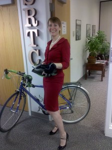 Barb wearing a red suit and black patent leather high heels with her bike in the offices of the Spokane Regional Transportation Council.