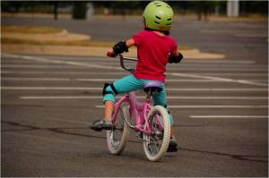 Little girl on a bicycle wearing a helmet.
