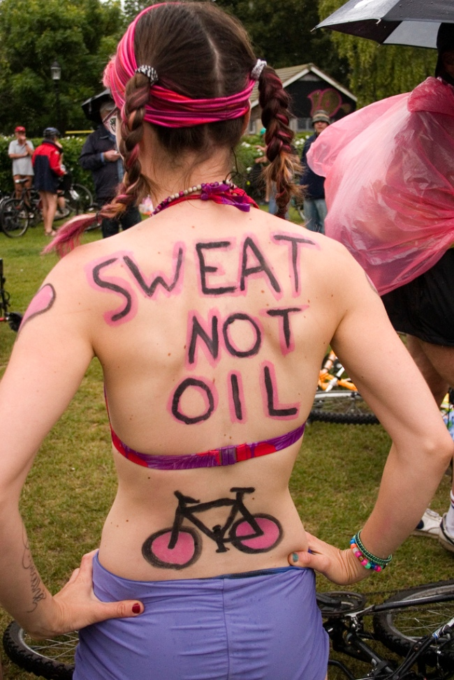 Woman with her back to the camera. Written on her back: Sweat Not Oil with a picture of a bicycle.