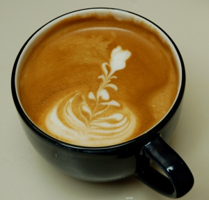 Latte with a flower design in the foam